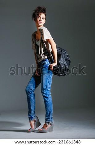 full-length girl in jeans with bag walking in studio  - stock photo