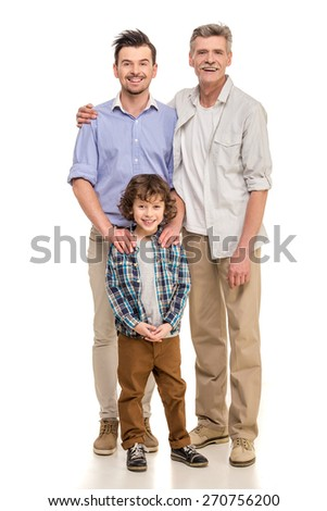 Full length. Grandfather, father and son looking at camera isolated a white background. - stock photo