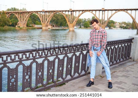 Full length handsome man, fashion model, with toupee posing outdoors with a bridge at background - stock photo