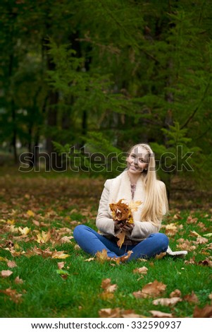 Full length, happy blonde woman in autumn park
