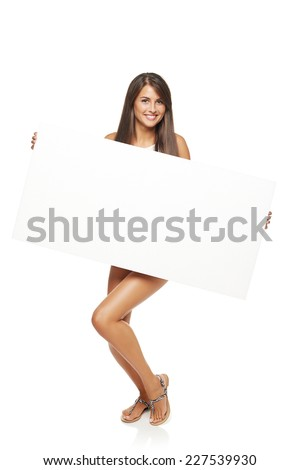 Full length happy woman standing holding white board banner over white background - stock photo