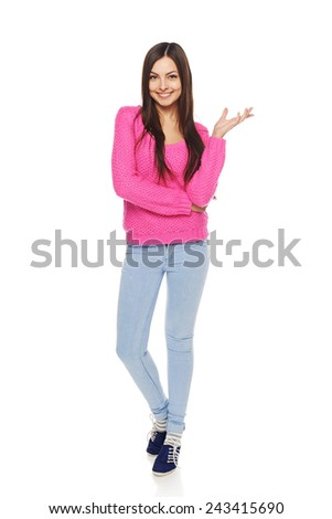Full length happy young female in blue jeans and pink sweater showing open hand palm with copy space for product or text - stock photo
