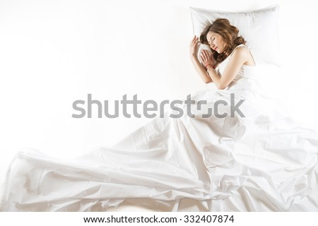 Full length high angle view of a young woman sleeping in bed in fetus position, isolated on white background - stock photo
