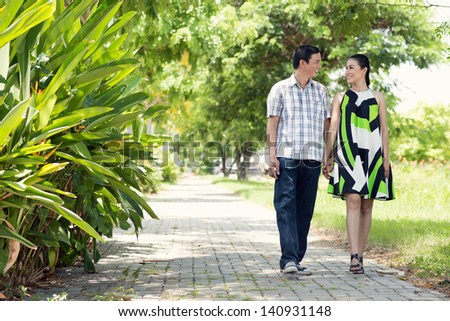 Full-length image of a couple walking in the park - stock photo