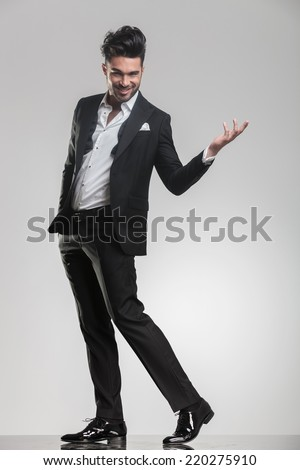 Full length image of a elegant man walking while holding one hand in the air and the other in his pocket. - stock photo