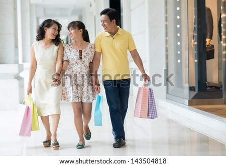 Full-length image of a happy family walking in the shopping-mall together - stock photo