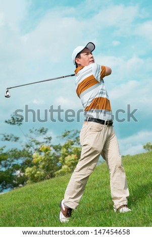 Full-length image of a man playing golf outside  - stock photo