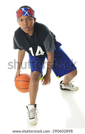 Full length image of a preteen basketball player looking at the viewer as he dribbles between his legs.  On a white background. - stock photo