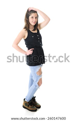 Full length image of a pretty teen brunette standing in her sleeveless black top, holey denim jeans and work boots.  On a white background. - stock photo