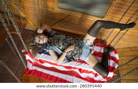 Full length image of a sexy slim blond woman lie on big American flag Skinny body of cute young adult girl with black pantyhose on legs rest on wooden table hang on metal chains Look at camera - stock photo