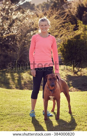 Full length image of a smiling senior woman wearing athletic clothing, standing outdoors on green grass with trees in the background and gentle sunlight, with hand resting on the back of her pet dog