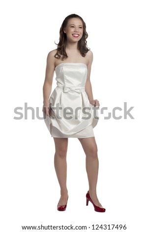 Full length image of a young female holding her white dress as she smiles