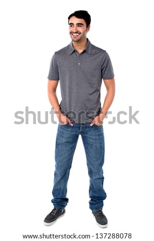 Full length image of a young guy standing with hands in jeans pocket. - stock photo