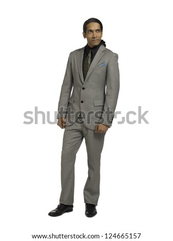 Full length image of an Asian businessman standing alone on a white background