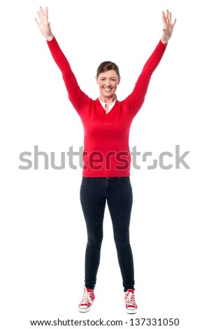 Full length image of an excited middle aged woman raising her arms.