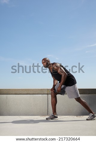 Full length image of fit and strong young male model ready for his run. Muscular male athlete outdoors.  - stock photo