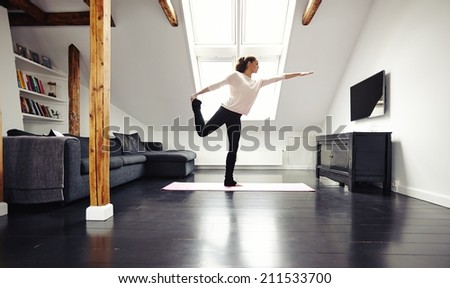 Full length image of fit young lady practicing yoga at home. Healthy young woman exercising in living room. Caucasian female model in warrior pose.