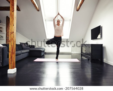 Full length image of fit young woman standing on one leg and meditating in her living room. Caucasian female doing yoga at home.