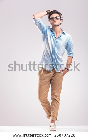 Full length image of handsome fashion man fixing his hat while looking up, holding one hand in his pocket. - stock photo