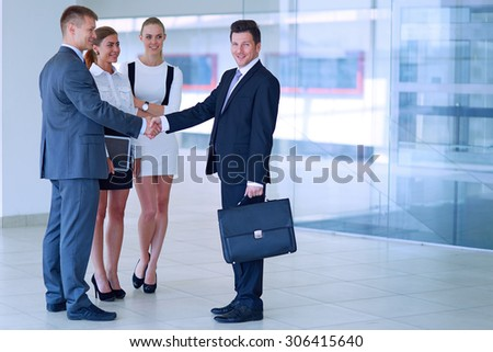 Full length image of two successful business men shaking hands with each other . - stock photo