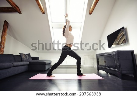 Full length image of woman standing on exercise mat with arms outstretched doing yoga at home. Healthy caucasian female model exercising indoors. - stock photo