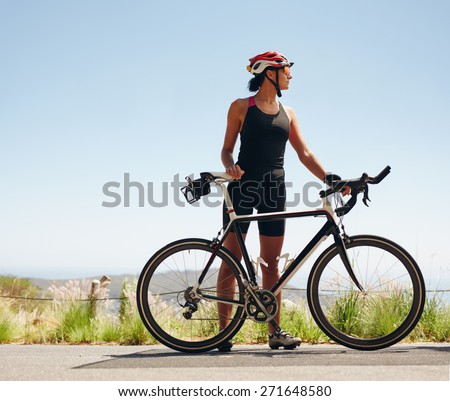 Full length image of young female cyclist looking away. Fit young woman wearing sportswear standing with her bicycle. - stock photo