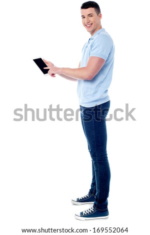 Full length image of young man using his tablet pc - stock photo