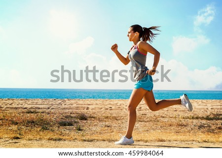 Full length in motion shot of attractive young woman jogging along beach front on sunny morning.