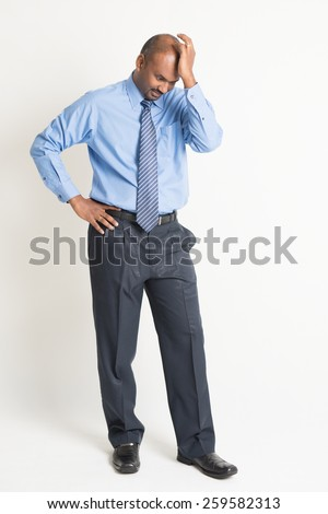 Full length Indian businessman hitting his head with hand, standing on plain background with shadow.