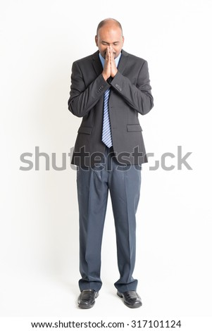Full length Indian businessman in praying gesture, standing on plain background. - stock photo