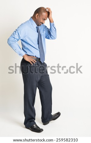 Full length Indian businessman with worried expression standing on plain background with shadow. - stock photo