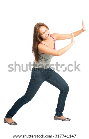 Full length isolated on white background of Asian woman in casual clothes with extended arms open palms, struggling, forcing, leaning, pushing against imaginary product placement object. Copy Space