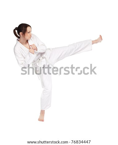 full-length isolated portrait of beautiful martial arts girl in kimono excercising karate kata kick
