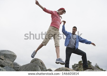 Full length low angle view of a young couple holding hands and jumping on rocks - stock photo