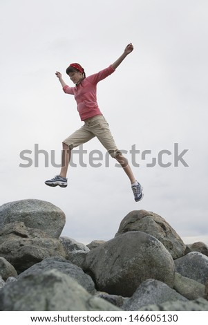 Full length low angle view of a young woman jumping with arms raised over rocks - stock photo
