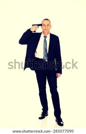 Full length mafia man with handgun near head. - stock photo