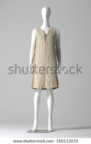 Full length mannequin dressed in sundress on gray background