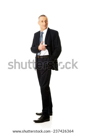Full length mature businessman pointing to the right. - stock photo