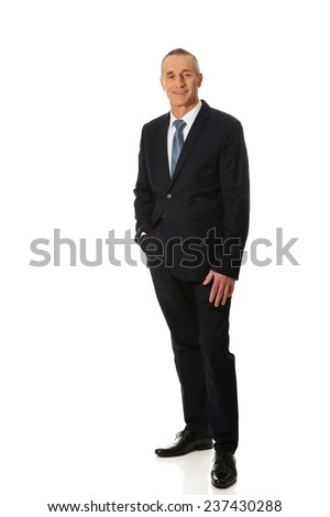 Full length mature businessman with hand in pocket. - stock photo
