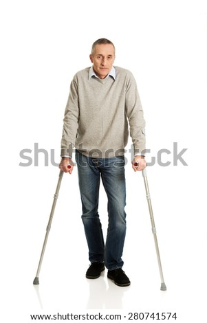 Full length mature man with crutches. - stock photo