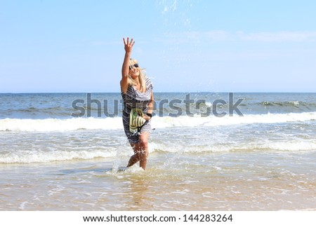 Full length mature woman with hat on beach enjoying summer holiday