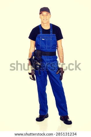 Full length mature worker with tool belt. - stock photo