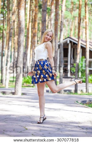 Full length of a beautiful young lady in skirt against summer forest background - stock photo