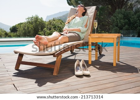Full length of a beautiful young woman relaxing on sun lounger by swimming pool - stock photo