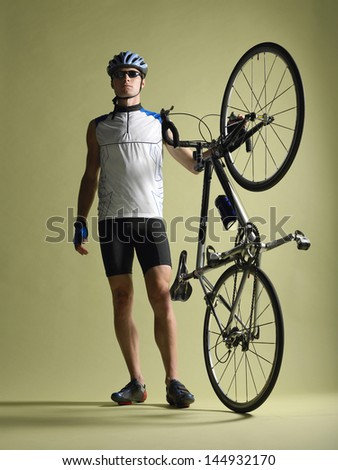 Full length of a bicyclist standing alongside bicycle against colored background - stock photo