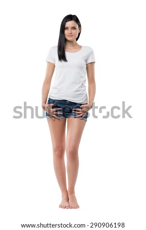 Full length of a brunette woman in a white t-shirt and denim shorts. Isolated. - stock photo