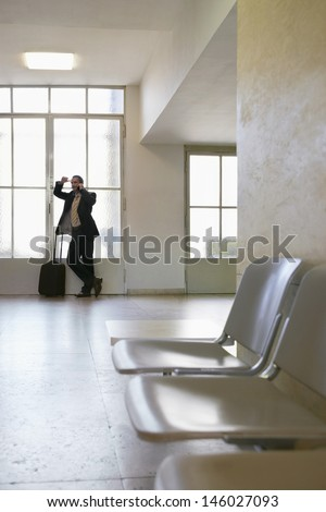 Full length of a businessman using mobile phone in the airport