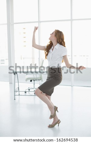 Full length of a cheerful elegant businesswoman cheering in a bright office - stock photo