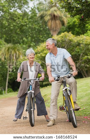Full length of a cheerful senior couple on cycle ride in countryside - stock photo