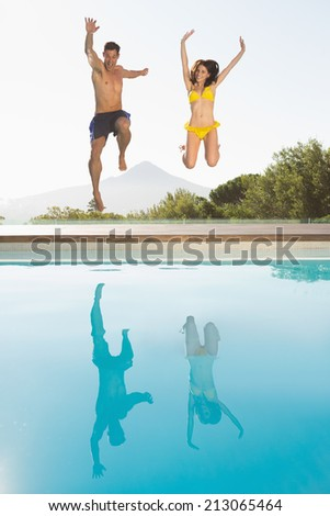 Full length of a cheerful young couple jumping into swimming pool - stock photo